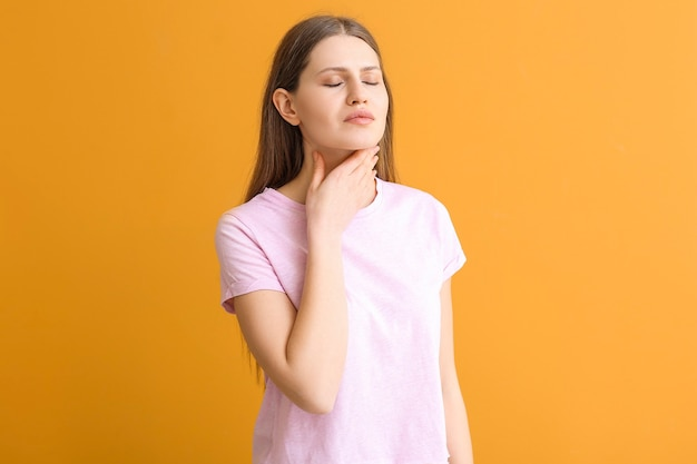 Young woman checking thyroid gland on color