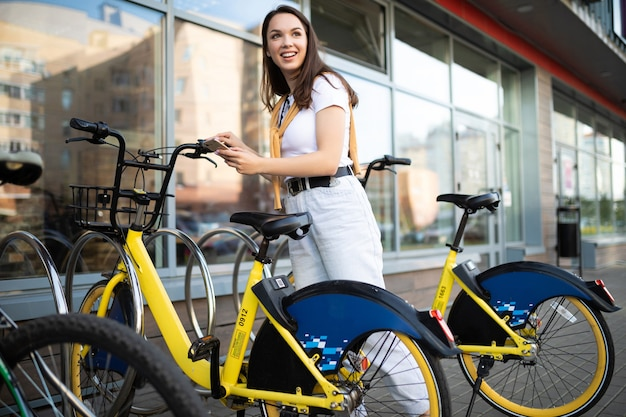 A young woman checks in a bike rental app in the city