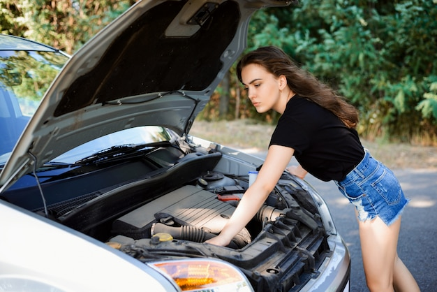Young woman checks car engine and tries to repair car by herself.