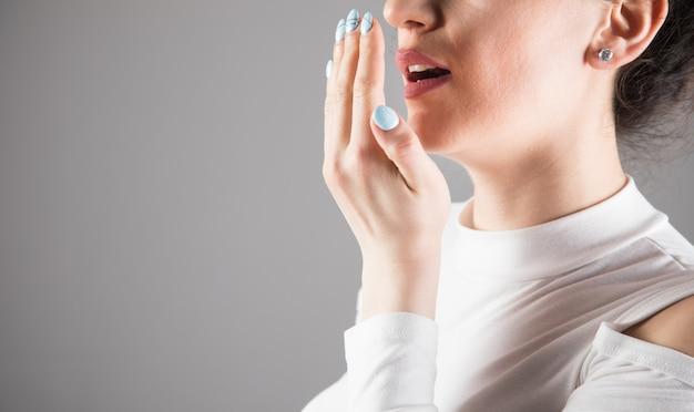 Молодая женщина проверяет дыхание на фоне серой сцены