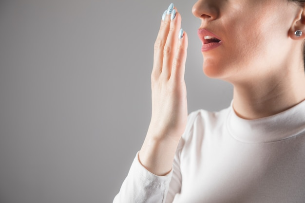Young woman checks her breath against a gray scene