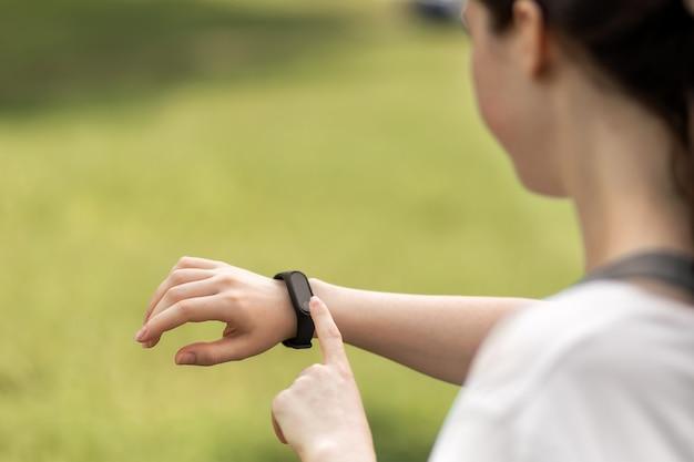 Молодая женщина проверяет свои умные часы. закройте руку с устройством. концепция современного устройства и велнеса