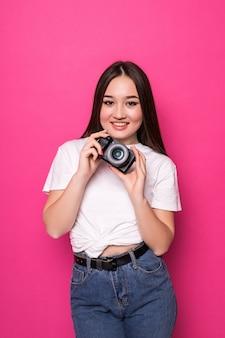 ピンクの壁の写真のカメラで陽気な若い女性