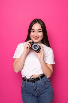 Young woman cheerful with photo camera on pink wall