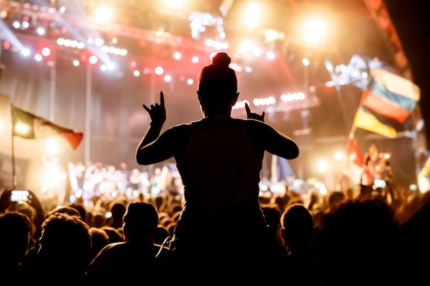野外コンサートで応援する若い女性