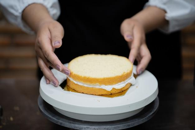 부엌에서 케이크를 요리하는 젊은 여자 요리사