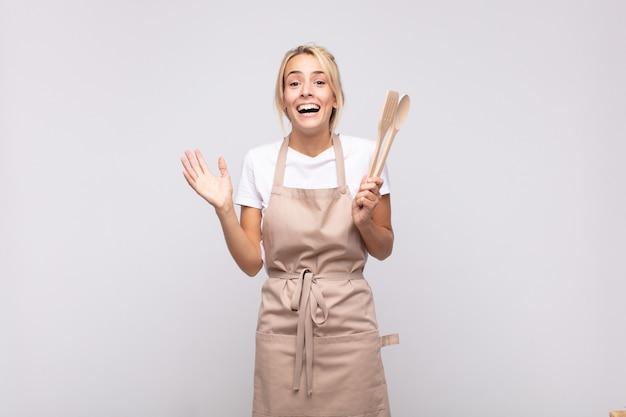 젊은 여성 요리사가 행복하고, 흥분하고, 놀라거나 충격을 받고, 웃고, 믿을 수없는 것에 놀란 느낌