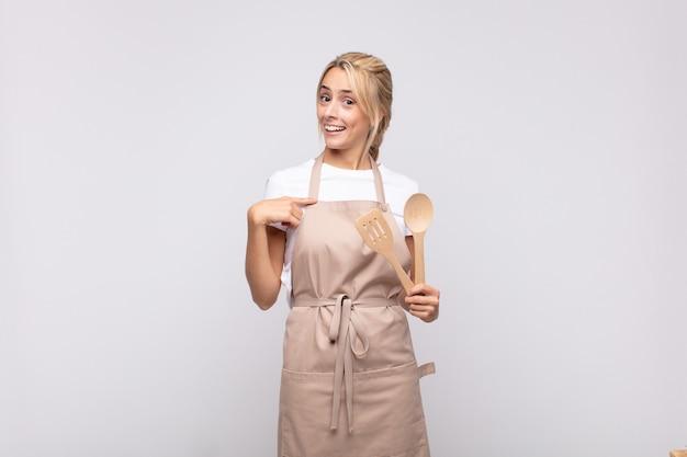 Молодая женщина-повар чувствует себя счастливой, удивленной и гордой, указывая на себя взволнованным, изумленным взглядом