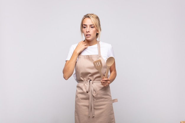 Молодая женщина-повар чувствует стресс, тревогу, усталость и разочарование, дергает за шею рубашки, выглядит разочарованной проблемой