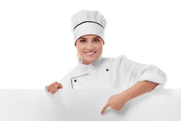 分離された白い空白のバナーを保持している若い女性シェフ