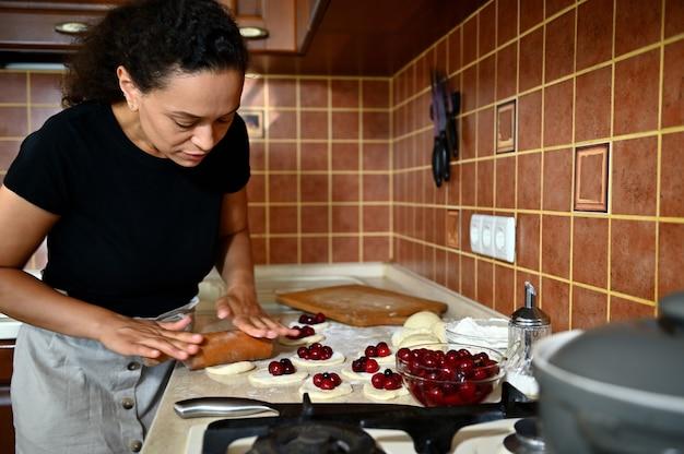 若い女性、パティシエ、麺棒でキッチンのカウンタートップに丸い形で生地を広げ、自家製のおいしい桜の餃子を準備します