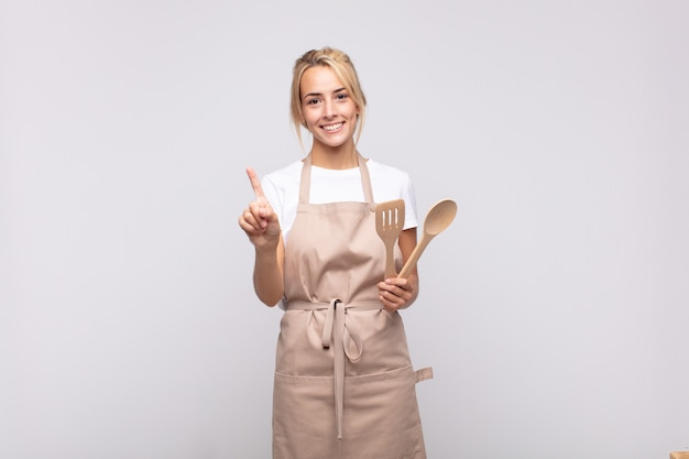 Young woman chef smiling and looking friendly, showing number one or first with hand forward, counting down