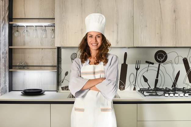 Young woman chef in toque and apron standing with folded arms in a modern fitted kitchen smiling at the camera