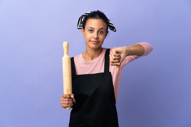 Young woman in chef uniform showing thumb down with negative expression