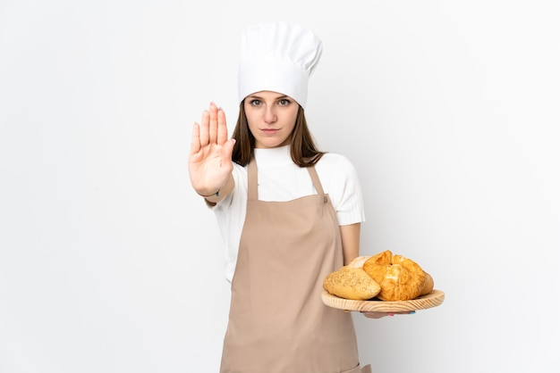 Young woman in chef uniform on white wall making stop gesture with her hand