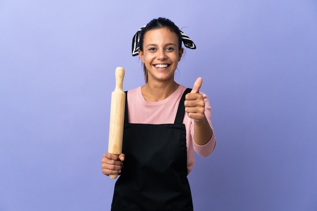Young woman in chef uniform with thumbs up because something good has happened
