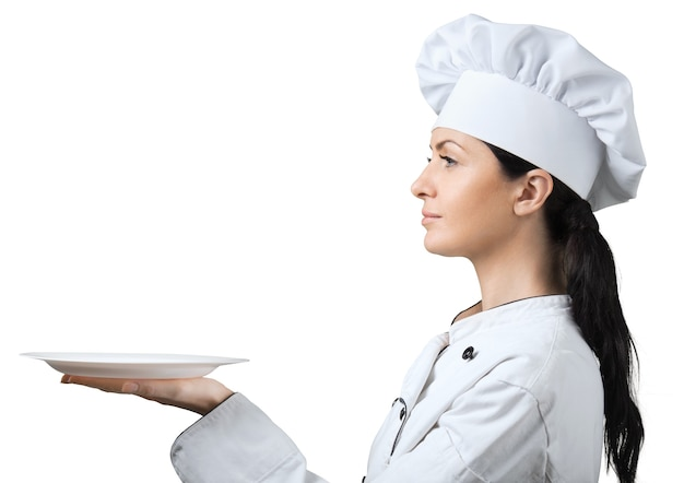 Young woman chef with empty plate on white background