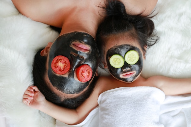 Young woman and child girl in black peeling face mask