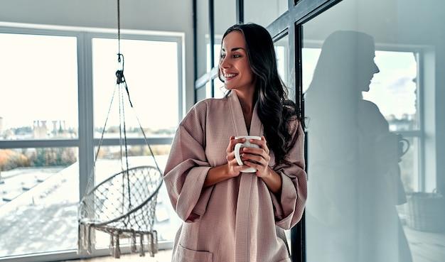 Молодая женщина отдыхает дома на фоне окна и висящего стула с чашкой кофе в руке. девушка расслабляется в гостиной, носить домашний халат.