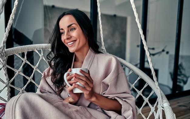 Молодая женщина отдыхает дома в удобном подвесном кресле у окна с чашкой кофе в руке. девушка расслабляется на качелях в гостиной на чердаке в домашнем халате.