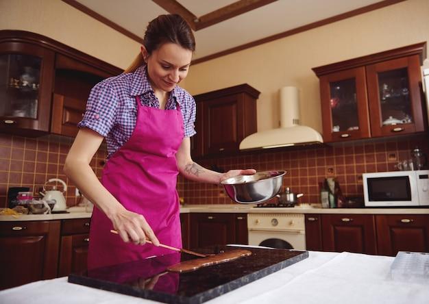 木製のキッチンの表面の大理石の表面に溶かしたチョコレートの近くにケーキスクレーパーを保持している若い女性のショコラティエ