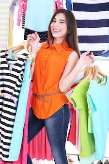 옷걸이 선반 근처 옷을 선택하는 젊은 여자