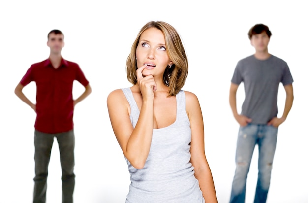 Молодая женщина выбирает из двух молодых людей, изолированных на белом