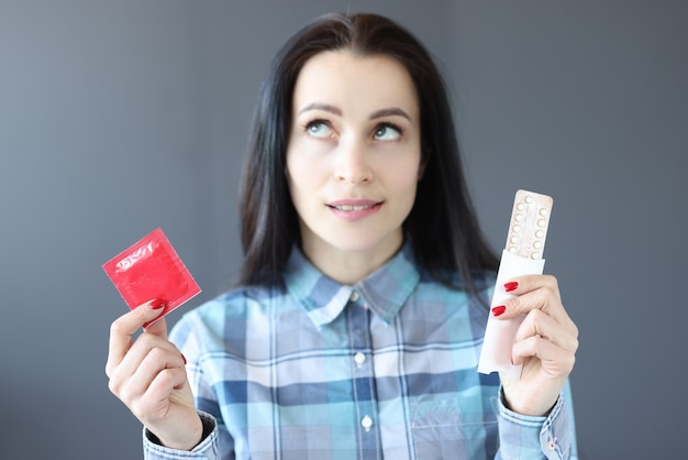 Young woman chooses between birth control pills and condom