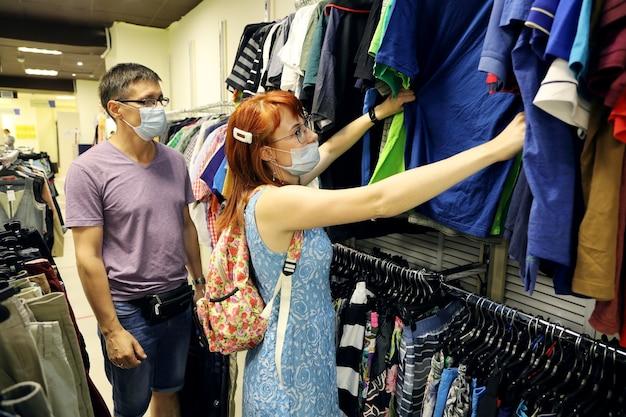 Молодая женщина выбирает одежду в отделе продаж