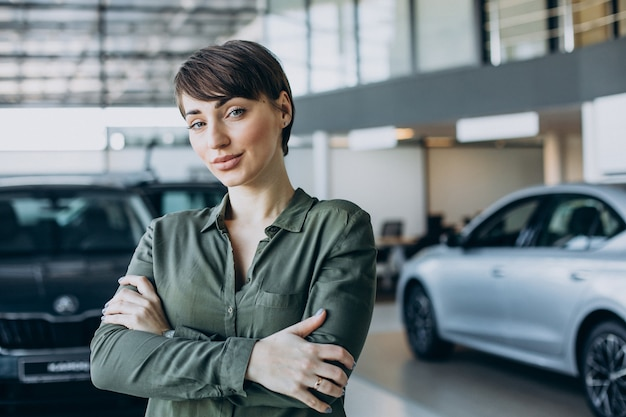Young woman choosimng a car in a car showroom