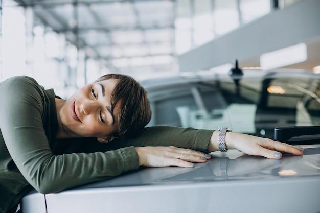 Giovane donna che sceglie un'auto in uno showroom di auto