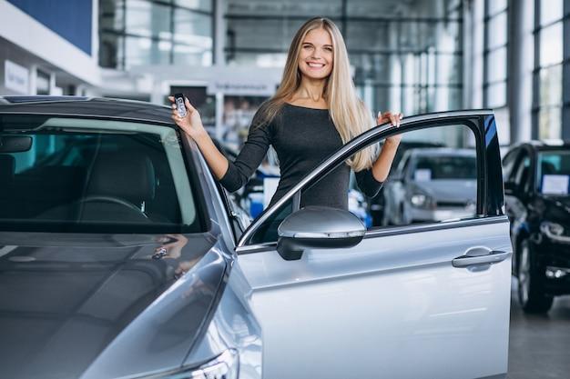 자동차 쇼 룸에서 자동차를 선택하는 젊은 여자
