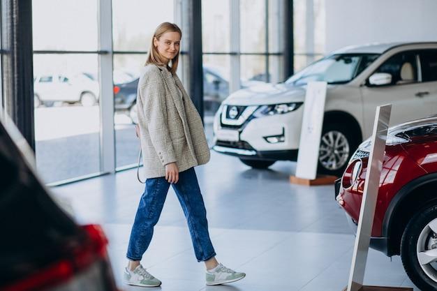 Молодая женщина, выбирая автомобиль в автосалоне