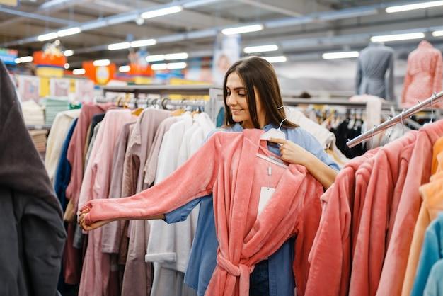 Молодая женщина, выбирая халат в магазине постельного белья. женщина покупает товары для дома на рынке, дама в магазине постельных принадлежностей