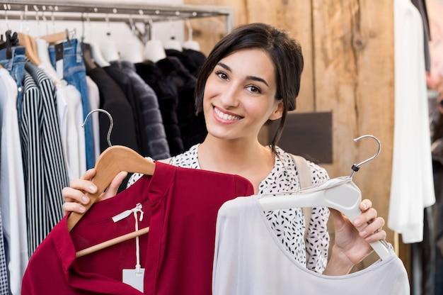 Молодая женщина, выбирая между платьями в магазине одежды