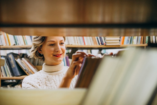 Young woman choosing book at the library