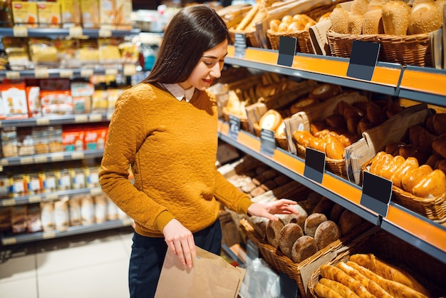 Young woman choosing bread in grocery store, bakery department