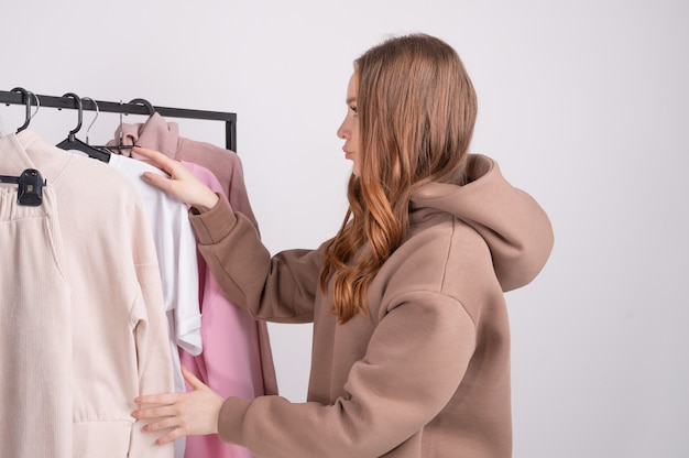 Молодая женщина, выбирая одежду в выставочном зале.