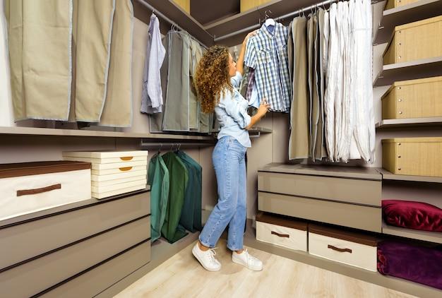 Молодая женщина выбирает одежду, которую нужно носить без перил в аккуратной гардеробной, смотрит на клетчатую рубашку на вешалке