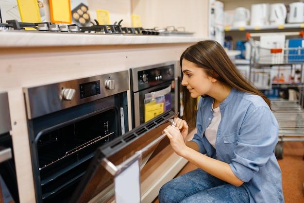 전자 제품 매장에서 전기 오븐을 선택하는 젊은 여자. 시장에서 가전 제품을 구입하는 여성 사람, 가게에서 물건을 찾는 주부