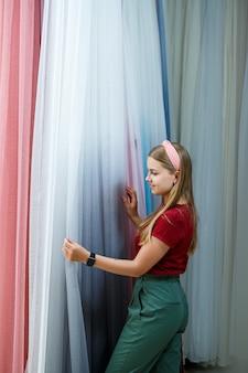 가게에서 새 커튼을 위한 천을 선택하는 젊은 여성. 커튼 샘플이 매장 레일의 옷걸이에 걸려 있습니다. 직물, 얇은 명주 그물 및 가구 실내 장식의 질감 샘플.