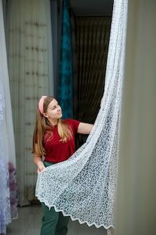 Молодая женщина, выбирая ткань для новых штор в магазине. образцы штор вешают на вешалках на рейку в магазине. образцы фактур ткани, тюля и обивки мебели.