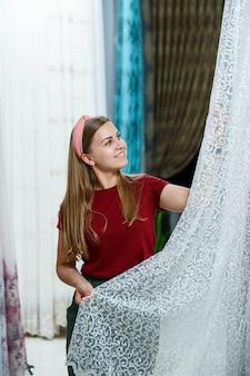 店で新しいカーテンの生地を選ぶ若い女性。カーテンのサンプルは、店内のレールのハンガーに掛けられています。生地、チュール、家具の装飾のテクスチャのサンプル。