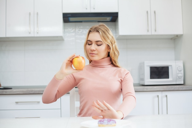 Young woman choosing between fruits and sweets