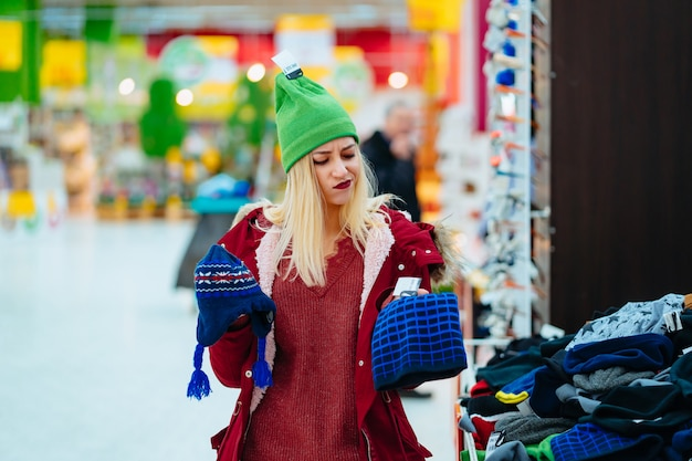 Young woman choosing hat in shopping center