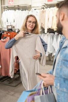 衣料品店で彼女のスタイリストの助けを借りて新しいドレスを選ぶ若い女性