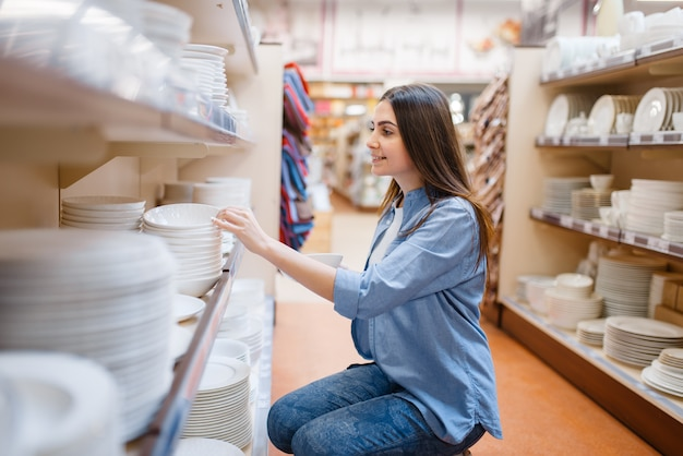 Young woman choosing plates in houseware store. female person buying home goods in market, lady in kitchenware supply shop