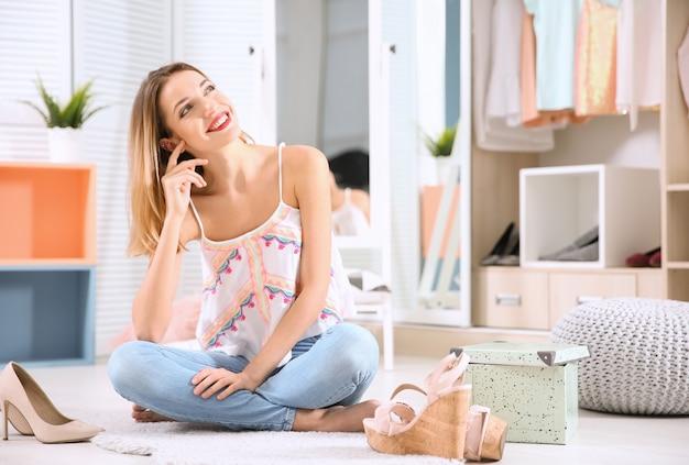 Молодая женщина, выбирая обувь в гардеробе дома