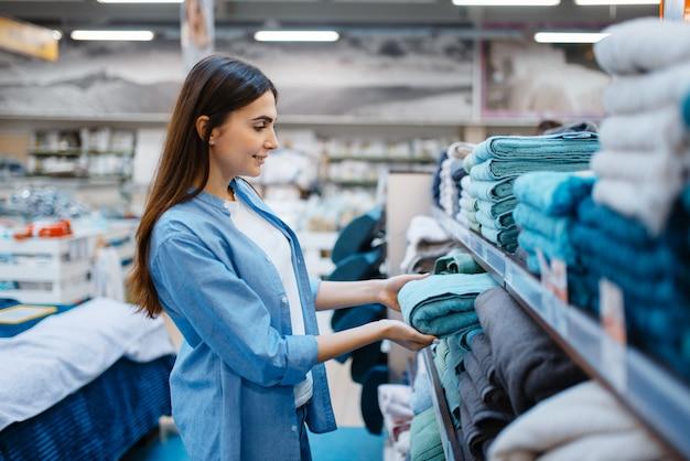 Молодая женщина, выбирая полотенце в магазине постельного белья. женщина покупает товары для дома на рынке, дама в магазине постельных принадлежностей