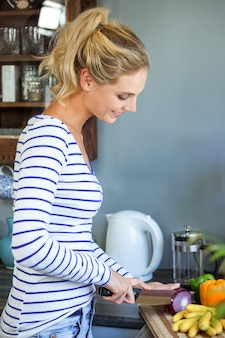 Молодая женщина, измельчения лука на кухне